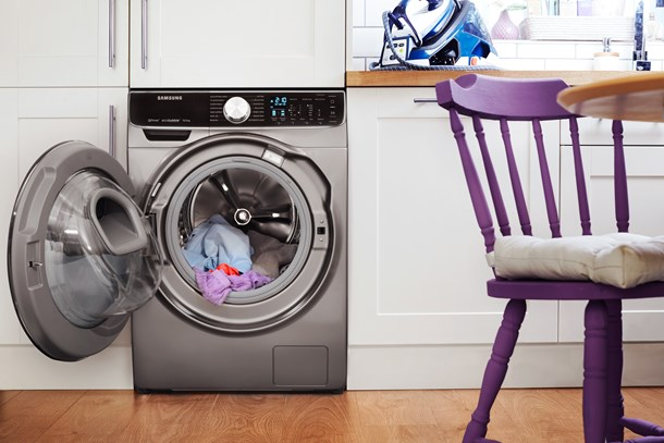 Open washing machine with clothes inside