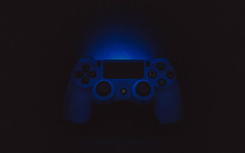 An image of a PS4 controller in low lighting