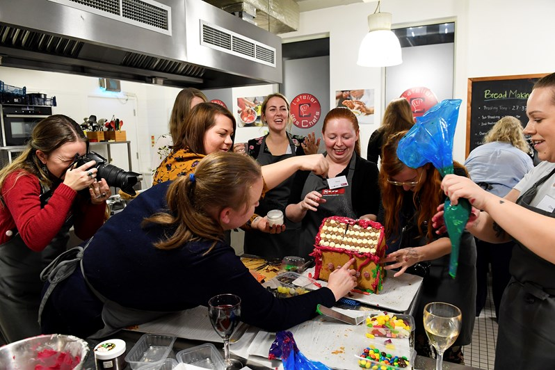 Bloggers gather around a gingerbread house at the NEFF Slide & Hide oven event