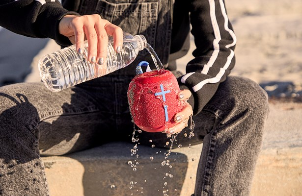 Water being poured over the waterproof UE WONDERBOOM 2 speaker