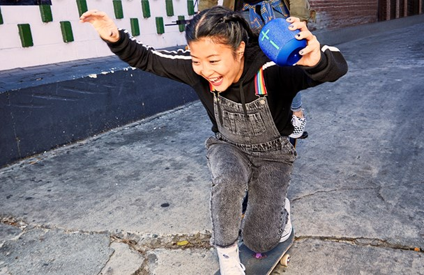 Girl riding a skateboard holding a UE WONDERBOOM 2