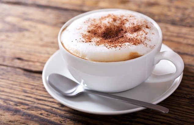 A cappuccino on a saucer with a teaspoon