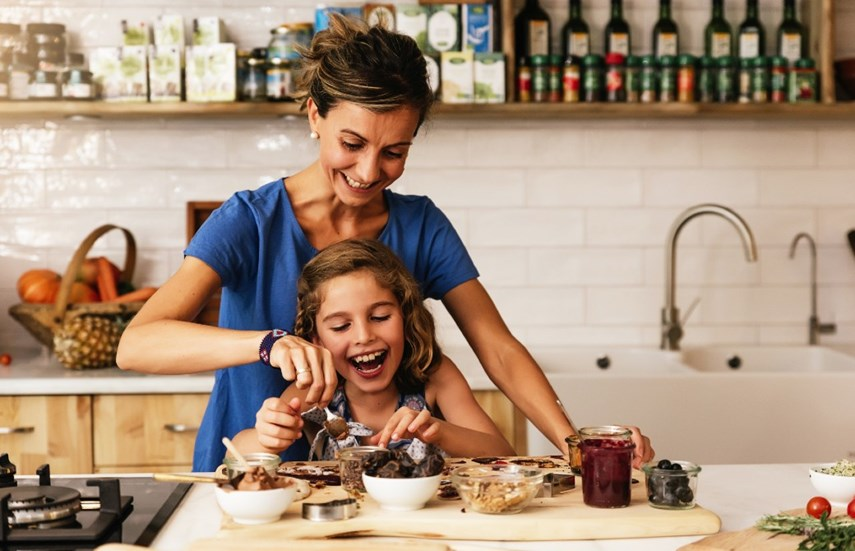 Mother and daughter stirring a bowl together in the kitchen.